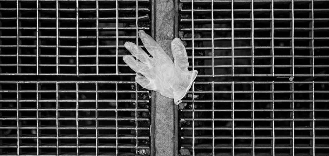 Discarded latex glove over subway grate